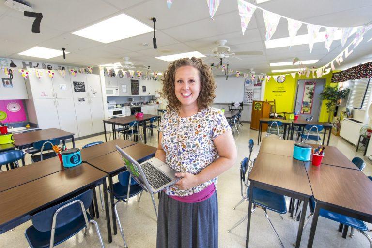 An elementary teacher working on a laptop in her classroom