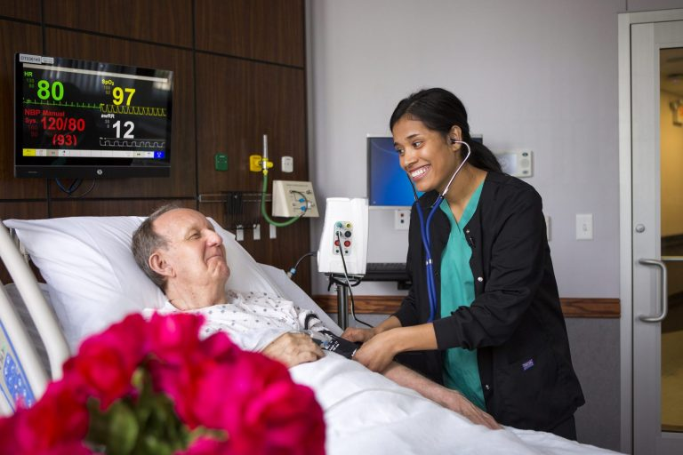 A nurse caring for a patient in a hospital room