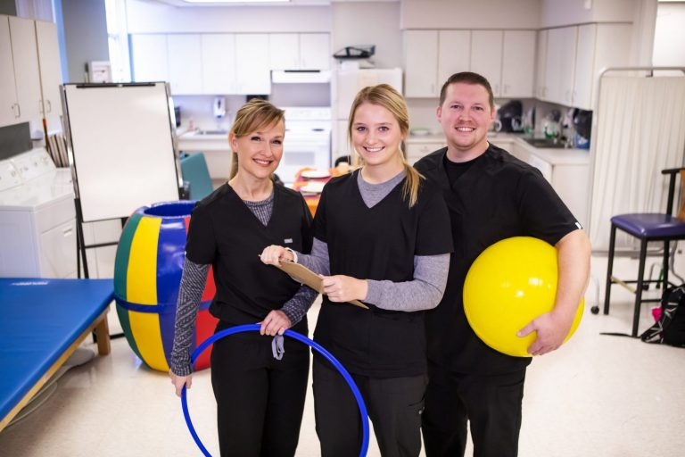 Occupational Therapy Assistant students working with exercise equipment