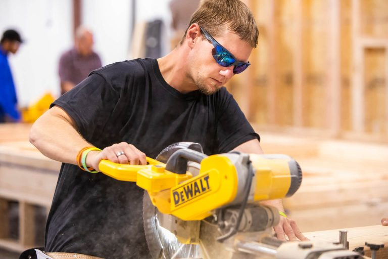 A carpentry student cutting wood with an electric saw