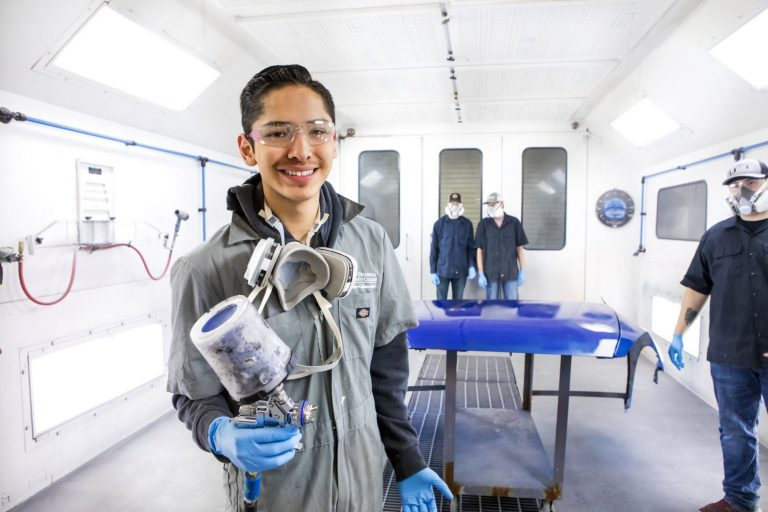 An auto collision repair technology student re-painting part of a car