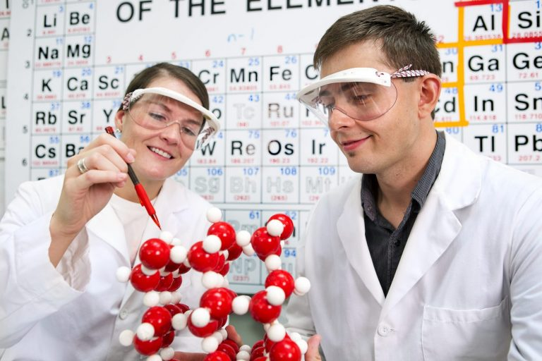 Chemistry students studying a science model together