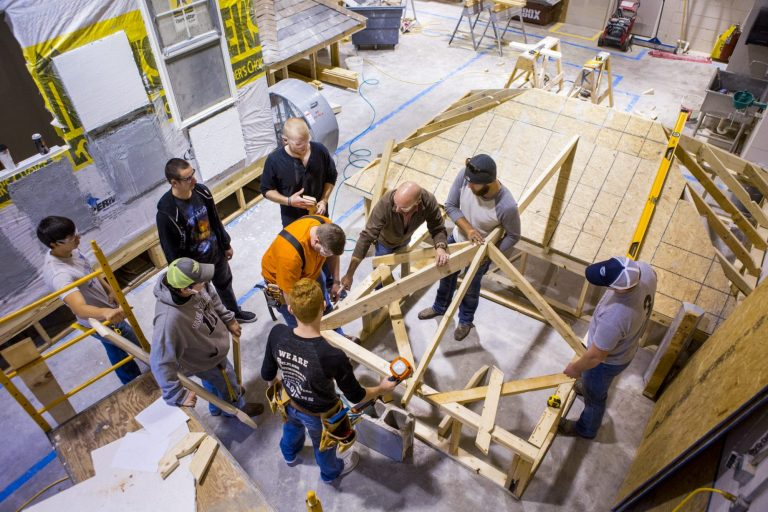 Construction technology students working together to assemble a wooden structure