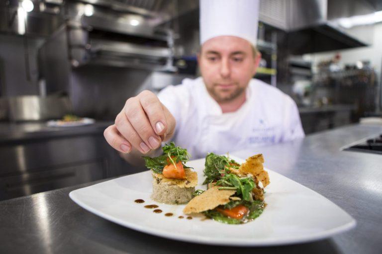 A culinary arts student garnishing a dish in a kitchen