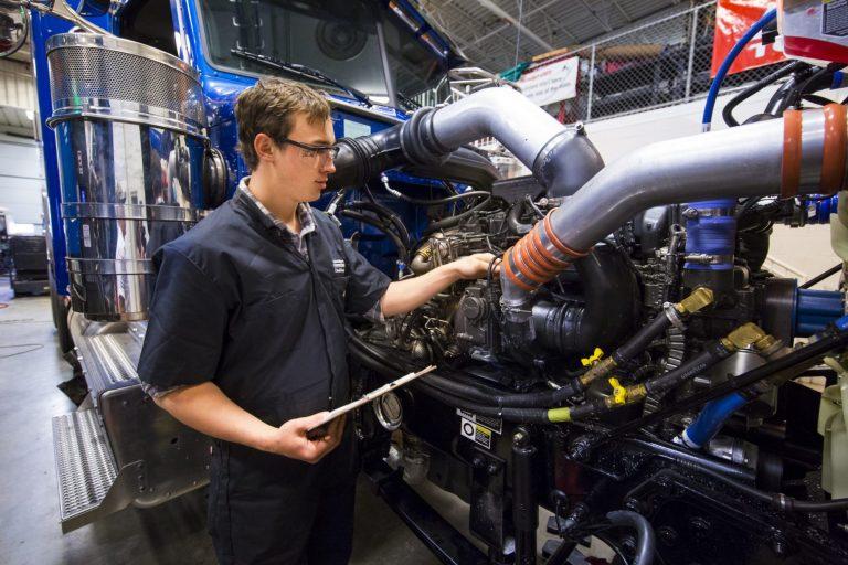 A diesel technology student repairing a diesel engine