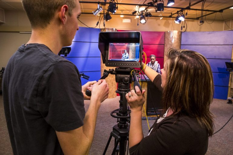 Electronic media production students filming a news broadcast