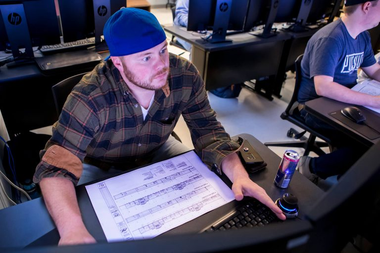 An engineering student using a blueprint for a project in a computer lab