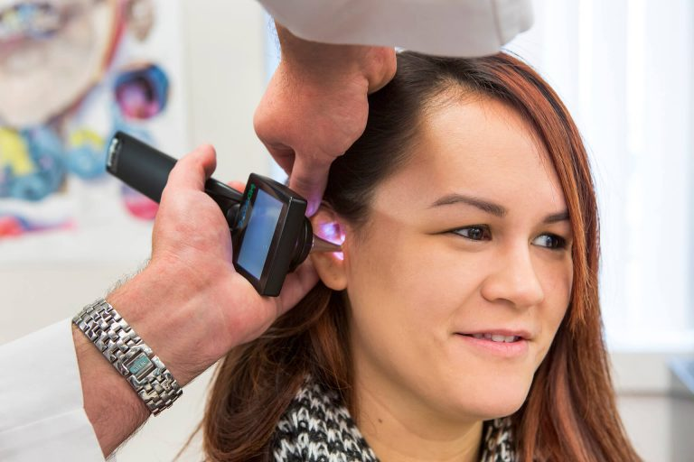 A medical professional using an otoscope on a patient's ear