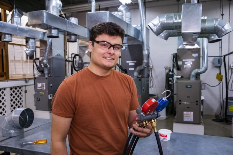 A heating, refrigeration and air conditioning student working with HVAC equipment