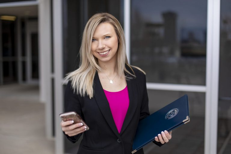 A hospitality management student working on her cellphone while holding a folder