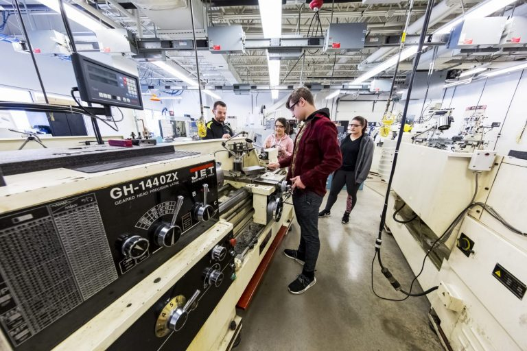 A manufacturing technology instructor training students to operate manufacturing equipment