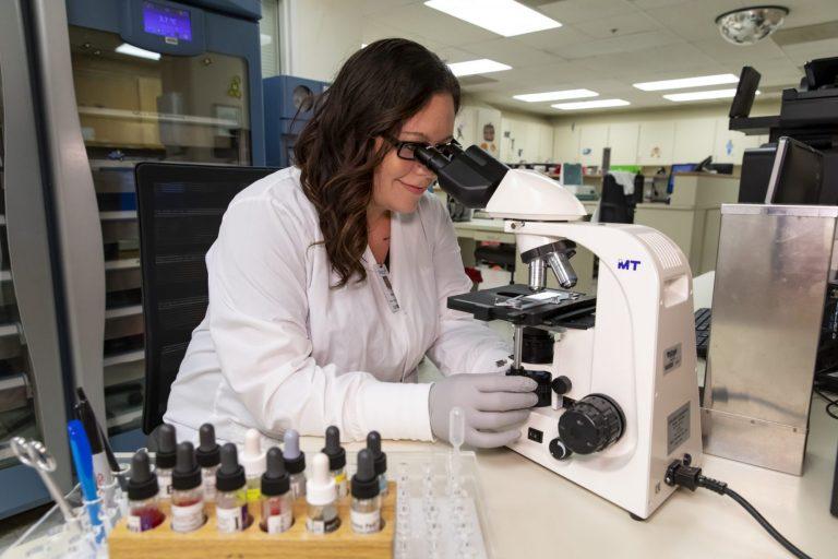 A medical laboratory technician using a microscope