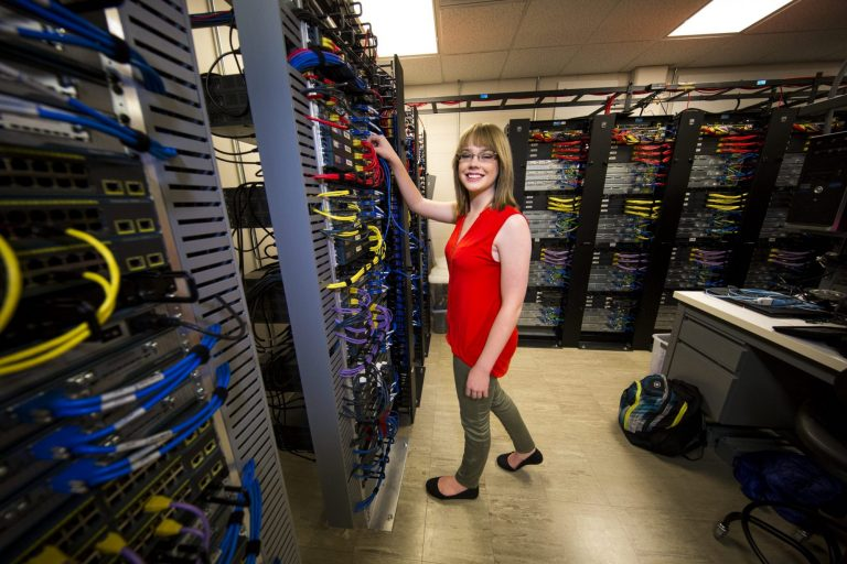 A networking technology student working in a room full of servers