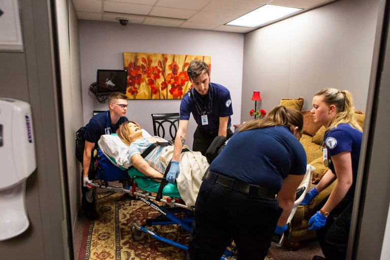 Paramedicine students practicing using a medical stretcher with a practice dummy