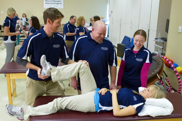 Physical therapy assistant students practicing a leg rehabilitation exercise on another student