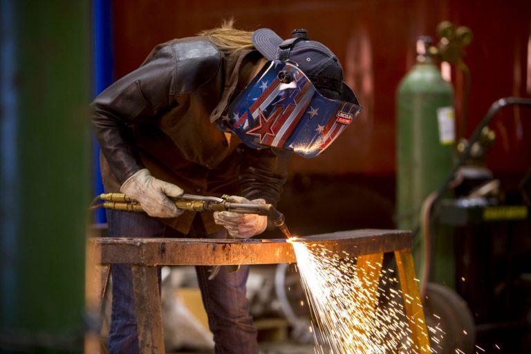 A welding technology student using a welding machine on a piece of metal