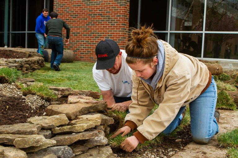 Turf and landscape management students building a garden rock wall