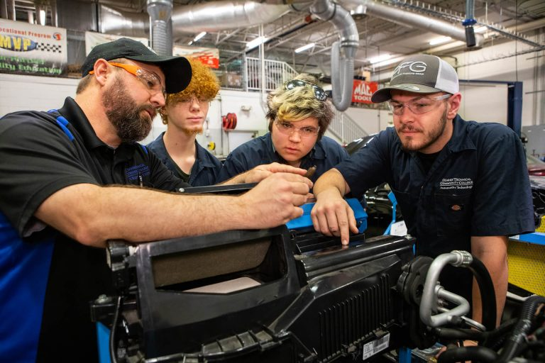 An automotive technology instructor showing students how to work on an engine