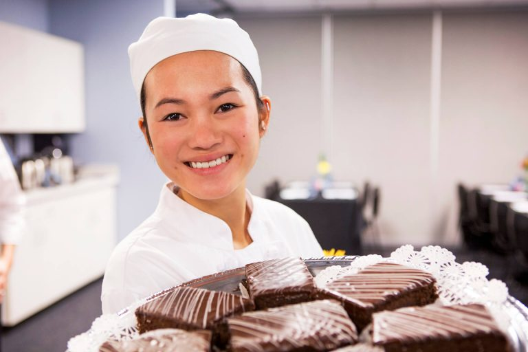 A culinary arts student displaying a plate of chocolates