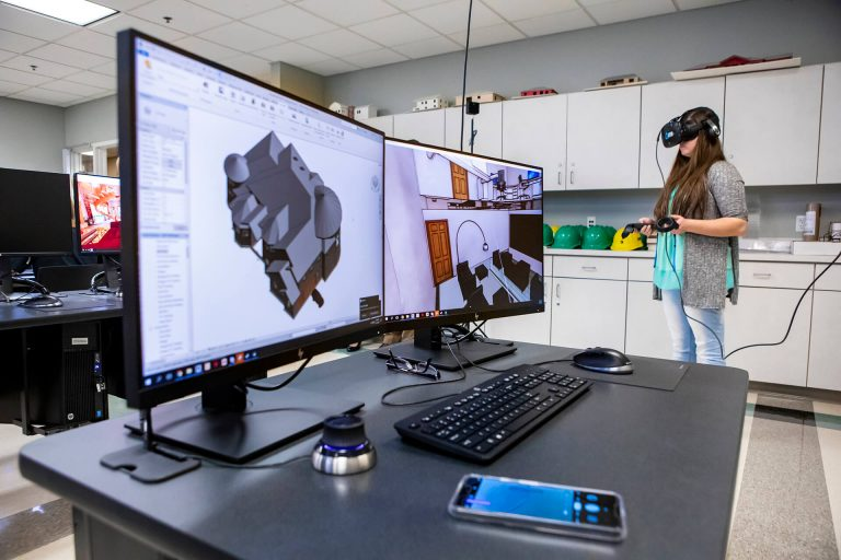 A drafting and design technology student viewing a building model through a virtual reality headset