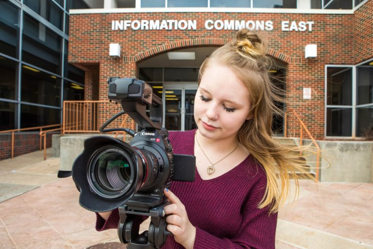 An electronic media production student taking a picture with a camera in front of the OTC Information Commons building