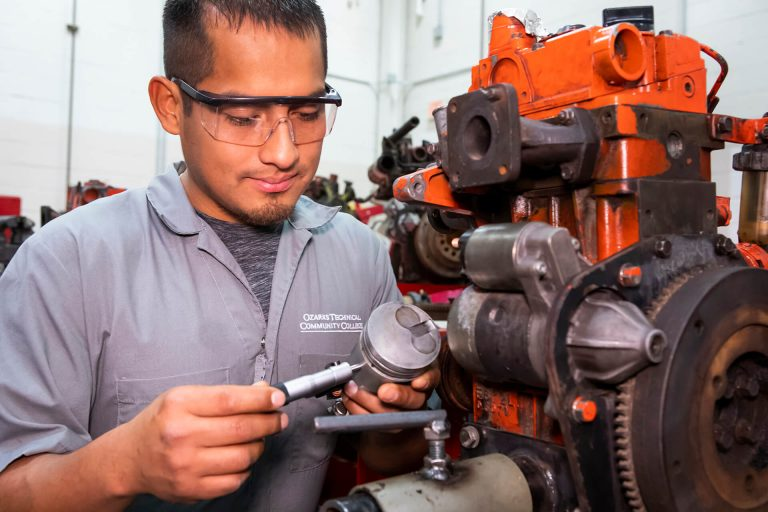 An outdoor power/powersports student working on an engine