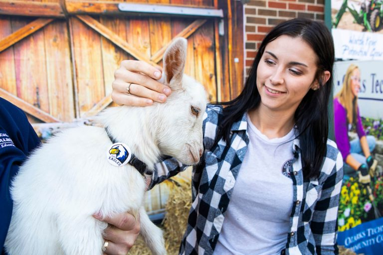 An agriculture student petting a goat in front of a barn