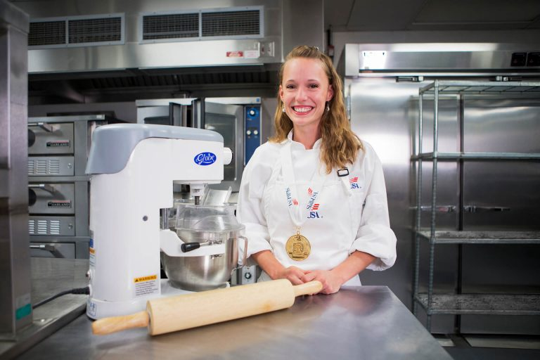A baking and pastry student using a stand mixer and rolling pin in a kitchen