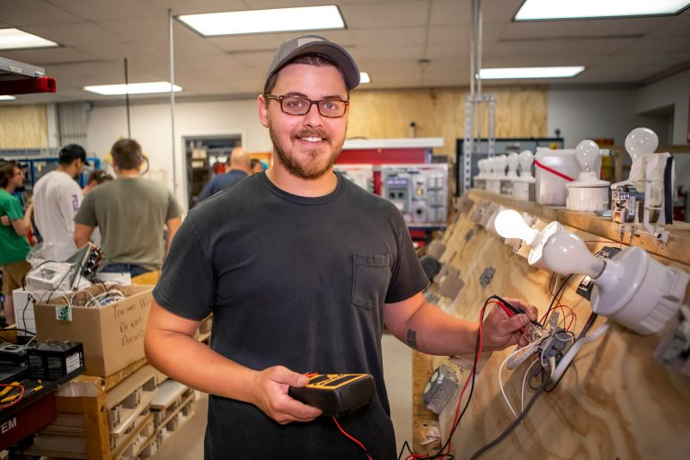 An electrical technician student working with electrical wiring in a classroom lab