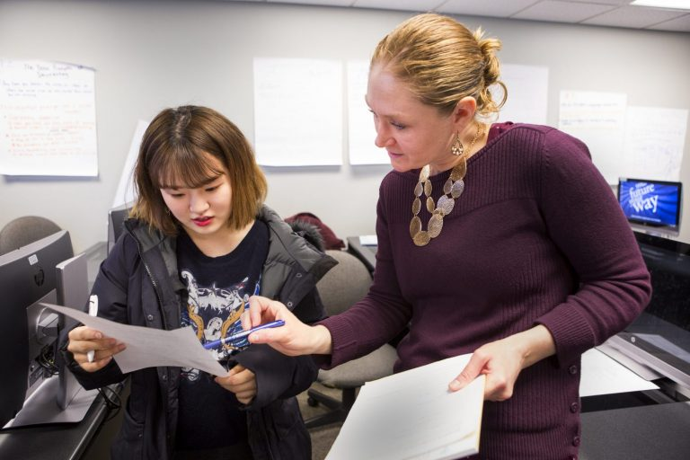 An English instructor talking with a student about her paper