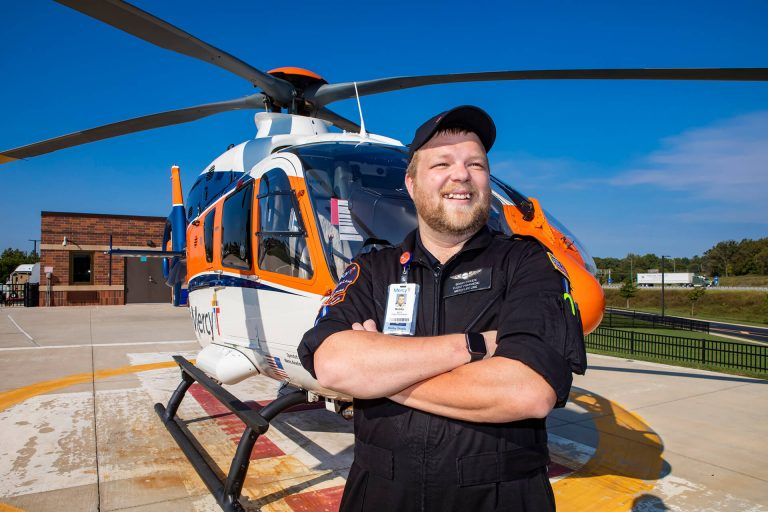 A critical care transport professional standing in front of a medical helicopter