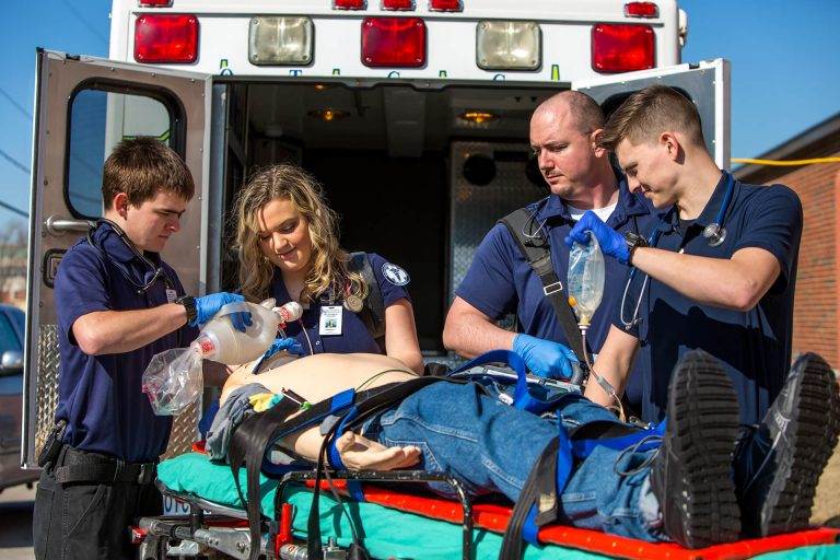 Paramedicine students practicing loading a dummy on a stretcher into an ambulance